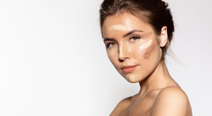 Waist up portrait of engaging young woman with cosmetic tonal foundation on her face. Glorious brunette looking at camera with calmness. Beauty treatment concept
