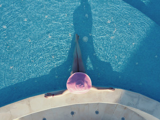 Young woman relaxing at swimming pool. Aerial photography