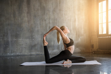 Printed kitchen splashbacks Yoga school Young woman doing ashtanga yoga practice in a loft studio, surrounded by bright sunlight. Beutiful girl meditating makes herself a healthy body and strengthening the spirit.