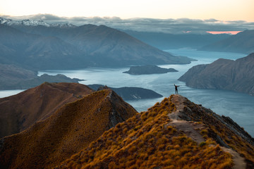 A woman looking at the beautiful landscape of the mountains and Lake Wanaka. Roys Peak Track, South Island, New Zealand.