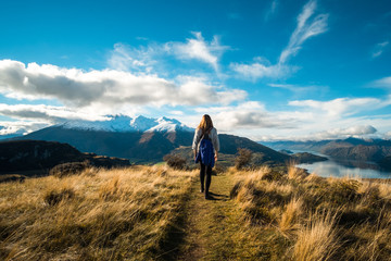 Wall Murals Blue jeans A hiker hiking on the beautiful track with a landscape of the mountains and Lake Wanaka. Roys Peak Track, South Island, New Zealand.