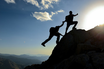 Help and assistance concept. Silhouettes of two people climbing on mountain and helping