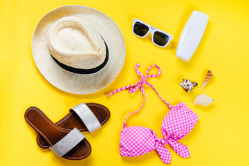 Top view of two pieces pink swimming suit and beach accessoties over yellow background.