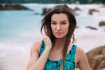 A portrait of a dark-haired, suntanned girl in a bright swimsuit, resting on the azure shore, has an expressive face, wears a stylish pendant in the form of a cross.