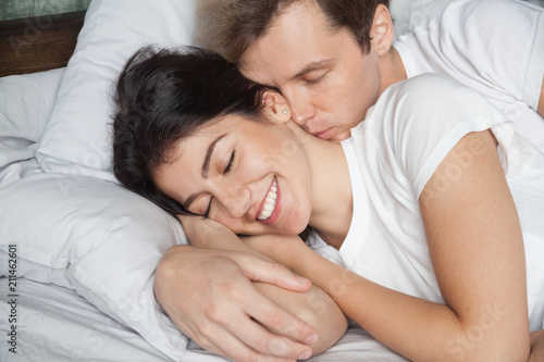 Romantic Young Husband Waking Up Beautiful Wife By Kiss In Neck