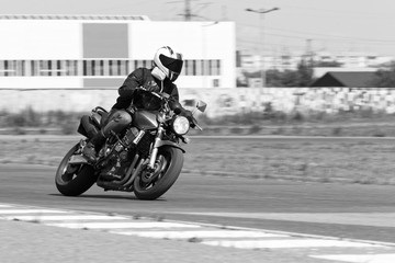 Man in a black jacket and grey pants race on a motorcycle. Motion blur. Black and white image.