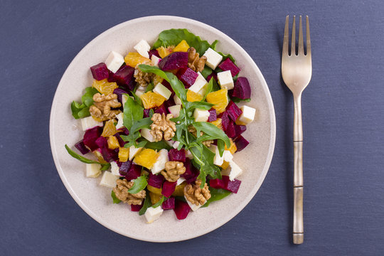 Healthy vegetarian salad with beetroot, green arugula, orange, feta cheese and walnuts on plate, top view