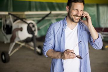 Young man using mobile phone in the airplane hangar