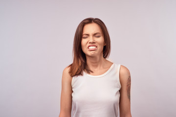 Picture of enraged dissatisfied young female grimacing, clenching teeth and making angry gesture while feeling furious at her cat that broke vase. Negative human emotions, feelings and reaction