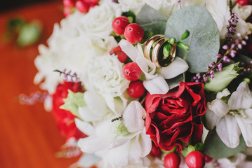 Beautiful wedding bouquet with rings on the wooden background