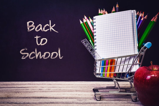 Back to School and Education shopping concept. classroom with apple, notebook and colorful pencils on chalkboard background. school border with copy space