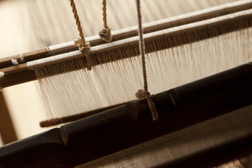 A close up image of an old weaving Loom and thread of yarn.