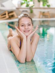 Happy teen girl lies near the pool