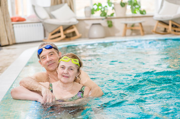 happy elderly couple in the pool. Space for text