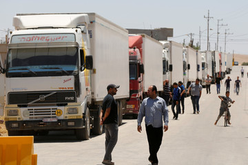 Trucks loaded with humanitarian supplies to be delivered for displaced Syrians, wait at the Jordanian city of Mafraq, near the border with Syria