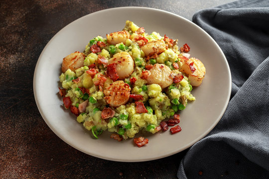 Fried scallops with mash potato, green peas and bacon