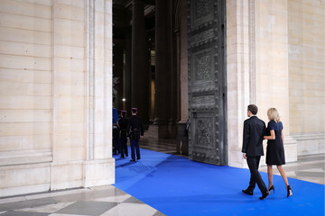 French President Emmanuel Macron and his wife Brigitte follow French Republican Guards who carry the flag-draped coffins of late Auschwitz survivor and French health minister Simone Veil and her late husband Antoine Veil during a national tribute in Paris