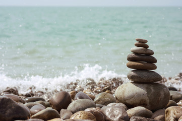Pyramid of stones against the background of the sea with horizon