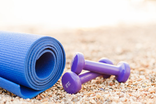 Two purple dumbbells and blue fitness yoga mat on stone and pebble sea beach. Sport background. Concept of healthy lifestyle and traveling. Sport female equipment. Copy space.