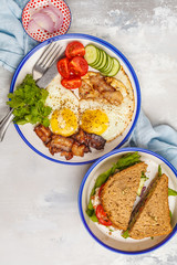 Fried eggs with bacon and a sandwich with meat, cheese and vegetables on white background, top view.