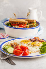 Fried eggs with bacon and a sandwich with meat, cheese and vegetables on white background. Delicious hearty breakfast.