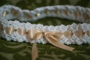 Cute baby girl head band in white with beige silk ribbon, cropped frontal view against an ornate cushion background, adorable accessory reserved for Christening or special events