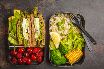 Healthy meal prep containers with feta sandwich with fruits, berries, rice and vegetables on dark background, top view.