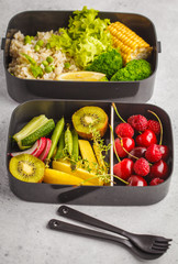 Healthy vegan meal prep containers with brown rice, broccoli, vegetables, fruits and berries