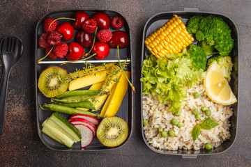 Healthy meal prep containers with brown rice, broccoli, vegetables, fruits and berries overhead shot with copy space