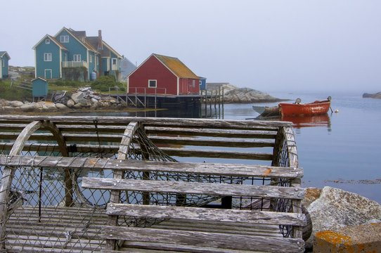 Wooden lobster trap on dock with row boats and houses lining harbor in background