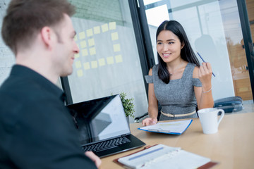 BUSINESS INTERVIEW WITH ASIAN WOMAN AND CAUCASIAN BOSS IN OFFICE