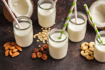Vegan alternative nut milk in glass bottles on dark background. Healthy vegan food concept.