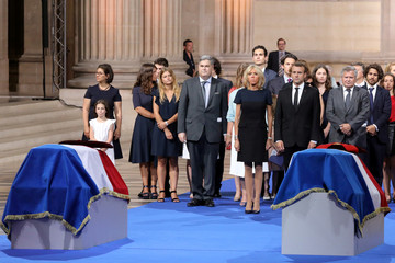French President Emmaniuel Macron, his wife Brigitte, stand with Pierre-Francois and Jean Veil, the sons of of late Auschwitz survivor and French health minister Simone Veil and her late husband Antoine Veil, during a tribute in Paris