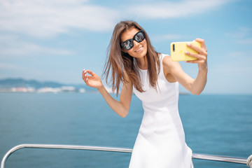 Amazing young woman with brown hair wearing white sexy dress making selfie with cell phone on yacht background.