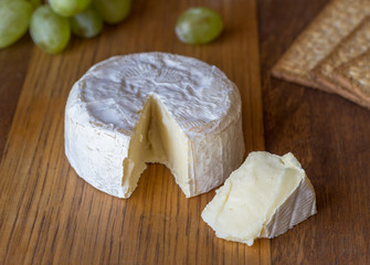 Camembert cheese and slice on wooden board