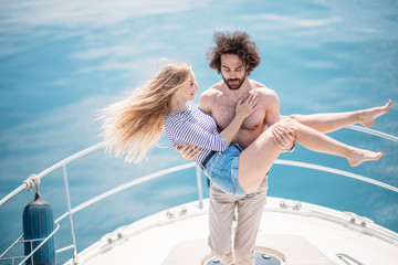 Playful couple chilling on a bow pleasure yacht. Half naked man holding on hands his girlfriend in shorts and stripped shirt over blue sea background in private boat have sea trip.
