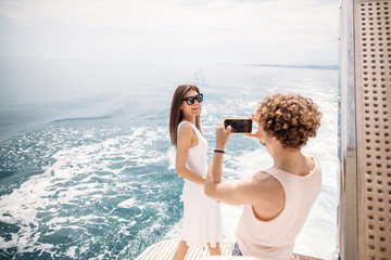 Young curly photographer taking picture of his girlfriend on seaboat, amazing seaviews on background - Man shooting girl outdoor in summer vacation trip over the sea