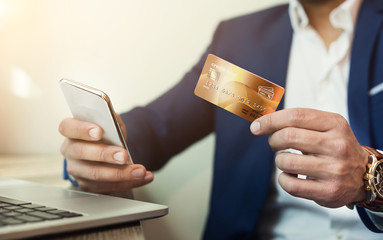 Businessman shopping online with credit card and mobile phone,