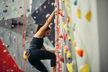 Side view of athletic woman practicing rock climbing on artificial wall indoors. Active lifestyle and bouldering concept.