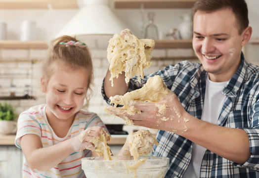 Father is cooking pastry with daughter