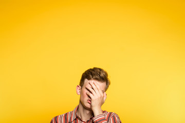 facepalm. ashamed abashed man covering his face with hand. portrait of a young guy on yellow background popping up or peeking out from the bottom. copy space for advertising.