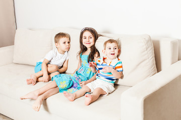 Photo of beautiful children on white modern couch.