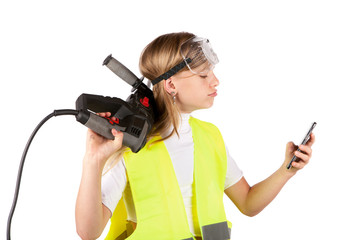 Cute young girl wearing safety vest and safety goggles holding a rotary hammer and using a smartphone
