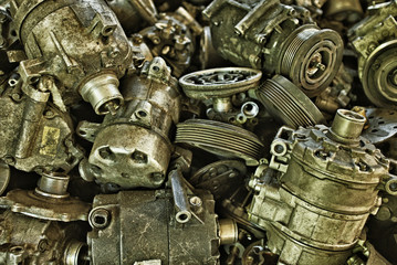 Vintage style industrial background – Lots of car parts like compressors, generators and small engines. HDR image with black gold filter.