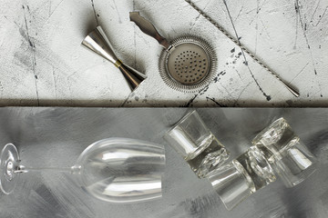 Set of bar accessories for making a cocktails arranged on a grey background