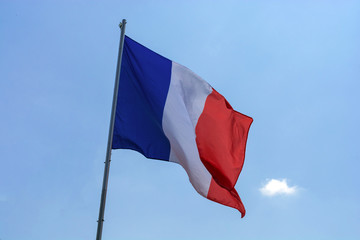 flag of France against a blue sky with clouds