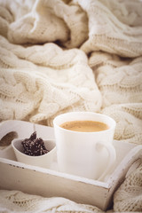 Hot beverage mug with chocolate cookies in a white wool blanket. Hot drink, cozy home and cold season concept