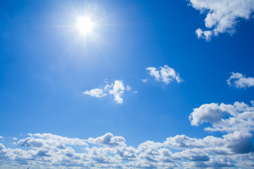 View of a fluffy clouds and sun in bright azure sky (background)