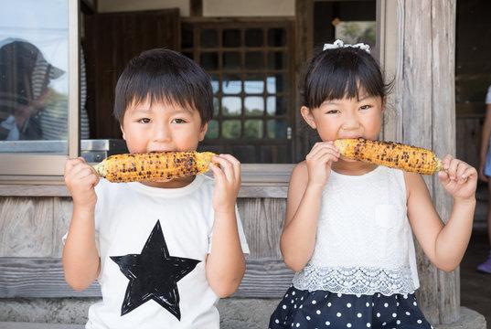 焼とうもろこしを食べる子供