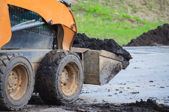 Close up view of a skid steer loader transports soil. Works on the improvement of the park area.